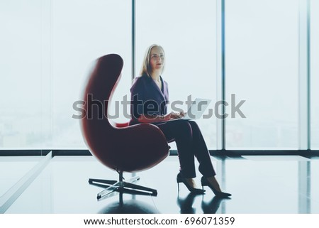 Portrait of attractive caucasian woman with straight hair sitting with laptop on armchair in office with smooth reflecting interior near panoramic window and looking aside, urban skyline in background