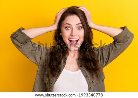 Portrait of attractive cheerful amazed girl great sudden news reaction isolated over bright yellow color background