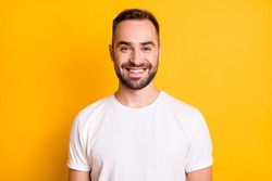 Portrait of attractive cheerful bearded guy freelancer wearing white tshirt isolated over bright yellow color background