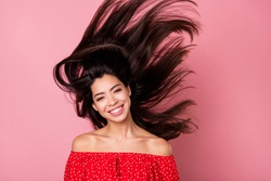 Portrait of attractive cheerful brunet girl having fun wind blowing long hair isolated over pink pastel color background