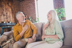 Portrait of attractive cheerful couple sitting on sofa talking having fun laughing at modern loft industrial interior home indoor