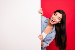 Portrait of attractive cheerful curious girl holding big blank poster ad promo isolated over bright red color background