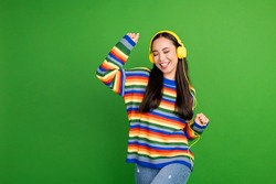 Portrait of attractive cheerful dreamy girl enjoying listening melody dancing having fun isolated over vivid green color background