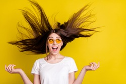 Portrait of attractive cheerful girl having fun wind blowing silky strong hair isolated over bright yellow color background