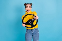 Portrait of attractive cheerful girl holding in hands steering wheel having fun isolated over bright blue color background
