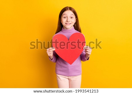 Portrait of attractive cheerful red-haired girl holding in hands big large heart card symbol isolated over bright yellow color background