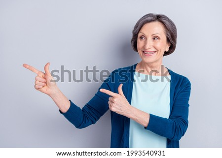 Portrait of attractive cheerful woman demonstrating copy space ad new novelty offer isolated over grey color background