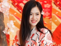 Portrait of attractive Chinese woman wearing traditional Japanese Kimono, smiling at camera, oriental beauty.