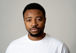 Portrait of attractive, confident african american young man looking neutral relaxed and serious in facial expressions, human emotions, Success and education concept. Isolated on grey background.