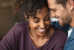 Portrait of attractive couple embracing each other. Closeup loving multiethnic couple embracing and kissing. Closeup face of cheerful boyfriend and african girl cuddling in love at home.