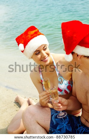 Portrait of attractive couple in Santa caps celebrating xmas on the beach