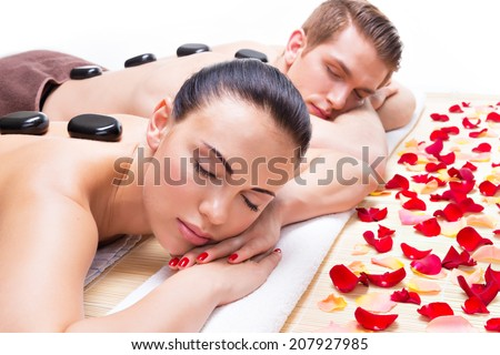 Portrait of attractive couple relaxing in spa salon with hot stones on body.  #207927985
