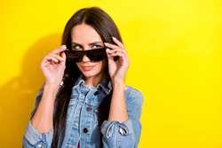Portrait of attractive cunning girl touching specs looking aside copy space isolated over bright yellow color background