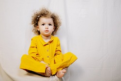 Portrait of attractive cute baby dressed in yellow dress posing on light background in home improvised photo studio