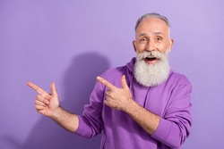 Portrait of attractive elderly retired trendy grey-haired man showing copy blank space isolated over purple violet color background
