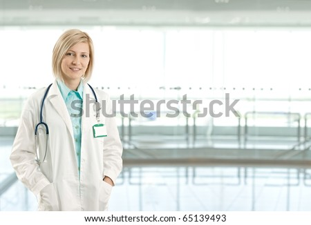 Portrait of attractive female doctor on hospital corridor looking at camera smiling. Copy space on right.?