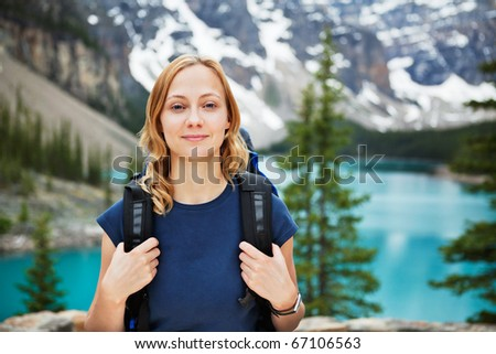 Portrait of attractive female hiker with her backpack against scenic view