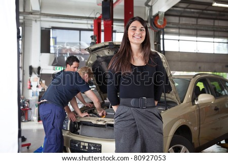 Portrait of attractive female in garage while people working in background