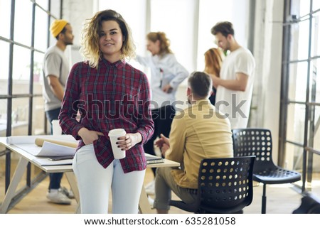 Portrait of attractive female leader dressed casual outfit posing for the camera during teamworking process with colleagues,skilled positive girl having brainstorming session in loft interior office #635281058