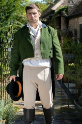 Portrait of attractive gentleman dressed in vintage costume, holding top hat in stately home courtyard