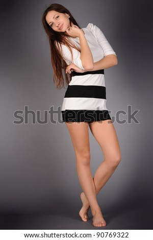 portrait of attractive girl in full growth on gray background