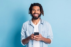 Portrait of attractive glad cheerful guy using device browse media free time isolated over bright blue color background