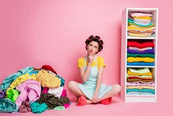 Portrait of attractive glamorous minded housemaid sitting on floor in messy untidy room thinking isolated pink pastel color background