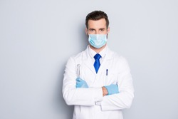 Portrait of attractive handsome dentist with hairstyle in protective face mask, white lab coat, blue tie, holding equipments in crossed arms, isolated on grey background