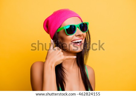 Portrait of attractive happy girl with glasses gesturing with fingers call me
