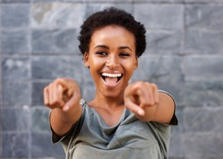 Portrait of attractive happy young black woman pointing fingers