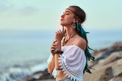 Portrait of attractive hippie woman wearing blue feathers in long hair, jewelry and white blouse with closed eyes. Indie boho chic style