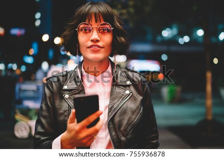 Portrait of attractive hipster girl in eyewear with night light reflection listening to music in earphones standing near copy space area for advertising, young woman enjoying playlist songs on mobile
