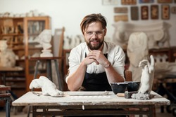 Portrait of attractive joyful bearded male sculptor which sitting on the workshop interior background and looks at the camera with smile.