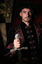 Portrait of attractive king with beard dressed in costume holding sword and looking at camera