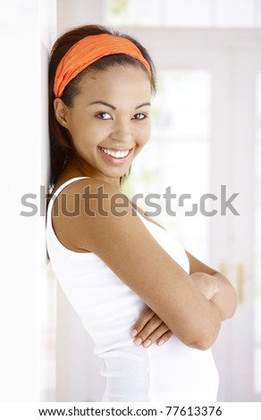 Portrait of attractive laughing ethnic woman standing at wall with arms crossed, smiling at camera.?