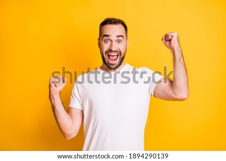 Portrait of attractive lucky cheerful bearded guy celebrating best luck isolated over bright yellow color background Foto stock ©