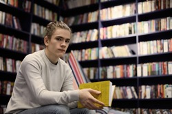 Portrait of attractive male student with hair knot choosing textbook in university library, searching for information for his diploma project, sitting isolated against bookshelves background