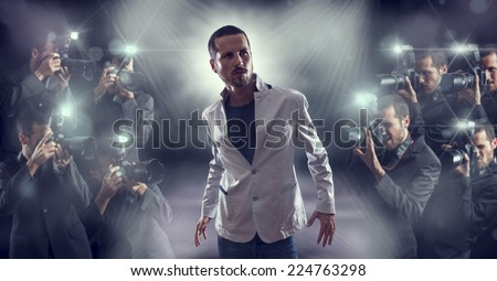 Portrait of attractive male vip celebrity posing in front of photographers paparazzi