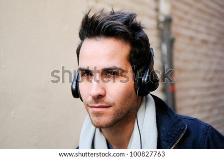 Portrait of attractive man in urban background listening to the music