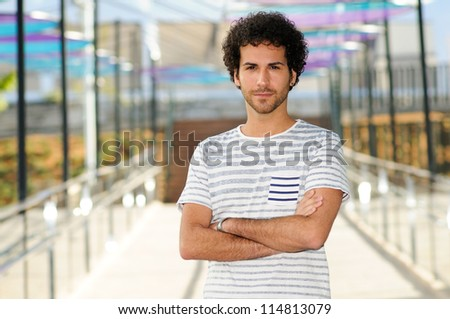 Portrait of attractive man with curly hairstyle in urban background