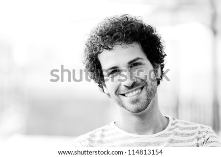 Portrait of attractive man with curly hairstyle smiling in urban background