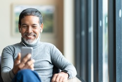 Portrait of attractive mature asian man retired with stylish short beard using smartphone sitting or listening music in urban lifestyle coffee shop. Old man using social network internet technology.