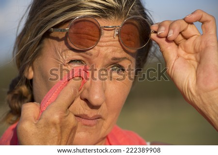 Portrait of attractive mature woman with sad and facial expression, looking concerned, wiping tears or dirt from eyes with tissue, holding glasses up with one hand, with blurred background outdoor.