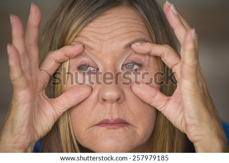 Portrait of attractive mature woman with tired and stressed facial expression, fingers keep eyes open, insomnia and headache, blurred background.