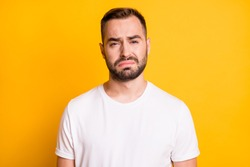 Portrait of attractive miserable capricious bearded guy feeling bad isolated over bright yellow color background