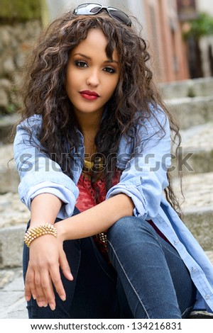 Portrait of attractive mixed woman in urban background wearing casual clothes