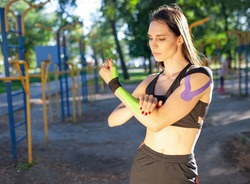Portrait of attractive muscular brunette woman wearing black sports outfit, looking aside. Young confident female athlete posing with arms crossed, colorful kinesiotaping on arms.