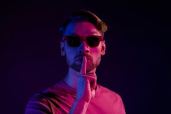 Portrait of attractive mysterious guy showing shh sign keep silence isolated over dark neon violet color background