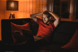 Portrait of attractive nerdy man with glasses is working late night on the computer in living room in home office