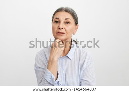 Portrait of attractive pensive mature female pensioner touching chin, thinking over her life plans and future, looking at camera with thoughtful facial expression. People, age and maturity concept